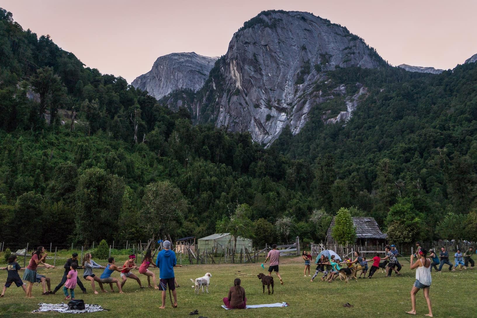 Se junta familias, niños, escaladores y excursionistas para un juego de tirar la cuerda en Camping La Junta.